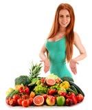 Junge Frau mit Vielzahl des organischen Gemüses und der Früchte Stockfoto