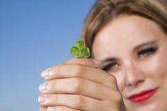Junge Frau mit vierblättrigem Kleeblatt Stockbild