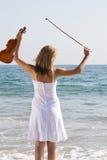 Junge Frau mit Violine auf Strand Stockfoto