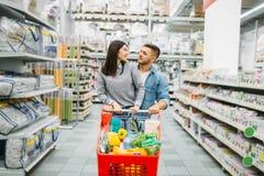 Junge Frau mit Wagen voll von Waren im Supermarkt lizenzfreies stockfoto