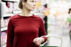 Junge Frau mit Warenkorb im Supermarkt Das Mädchen im Hintergrund des Speichers betrachtet die Waren Fahrwerkbeine und Frauenbeut Lizenzfreies Stockfoto