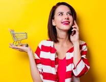 Junge Frau mit Warenkorb und Handy Lizenzfreie Stockbilder