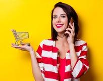 Junge Frau mit Warenkorb und Handy Stockbild