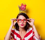 Junge Frau mit Warenkorb und Wecker Lizenzfreie Stockfotos