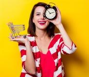 Junge Frau mit Warenkorb und Wecker Stockfotos