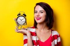 Junge Frau mit Warenkorb und Wecker Lizenzfreie Stockfotografie
