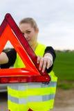 Junge Frau mit warnendem Dreieck auf Straße Stockbild
