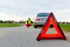 Junge Frau mit warnendem Dreieck auf Straße Lizenzfreies Stockfoto