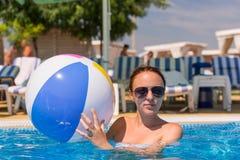 Junge Frau mit Wasserball im Swimmingpool Stockbild