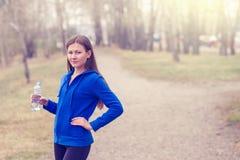 Junge Frau mit Wasserflasche in der Hand vor dem Lauf Eine gesunde Lebensart Sporteignungsyoga Stockfotografie