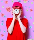 Junge Frau mit Wecker Stockfotografie