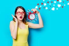 Junge Frau mit Wecker und abstrakten Herzen Lizenzfreie Stockbilder