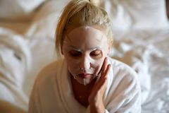 Junge Frau mit Weißbuchmaske beim auf Bett zu Hause sitzen lizenzfreie stockfotografie