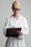 Junge Frau mit weißem Mantel schreibt auf ein Klemmbrett Lizenzfreie Stockfotos