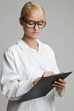 Junge Frau mit weißem Mantel schreibt auf ein Klemmbrett Stockbild