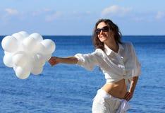 Junge Frau mit weißen Ballonen Stockfoto