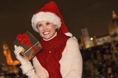 Junge Frau mit Weihnachtspräsentkarton in Florenz, das beiseite schaut Lizenzfreies Stockfoto