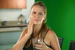 Junge Frau mit Zahnschmerzen kaltes Wasser trinkend Lizenzfreie Stockfotos