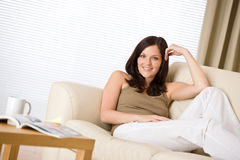 Junge Frau mit Zeitschrift und Kaffee im Aufenthaltsraum lizenzfreie stockbilder