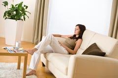 Junge Frau mit Zeitschrift und Kaffee im Aufenthaltsraum stockfoto