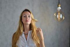 Junge Frau in modische Kleidung stehen zwischen Glühlampen Ungewöhnliches Kunstbild lizenzfreie stockfotografie