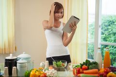 Junge Frau nach Rezept auf Digital-Tablet Lizenzfreie Stockfotografie