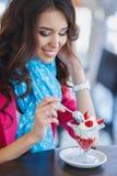 Junge Frau, NachtischEiscreme mit Erdbeeren Stockfotos
