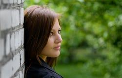 Junge Frau nahe Backsteinmauer Stockfoto