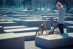Junge Frau nahe bei den gemieteten Fahrrädern, welche die Karte auf das Holocaustdenkmal, Berlin, Deutschland betrachten Stockbilder