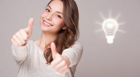 Junge Frau nahe bei Kreativitätssymbol Lizenzfreies Stockfoto