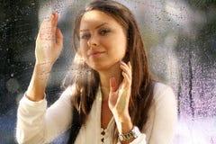 Junge Frau nahe dem Fenster nach dem Regen stockfoto