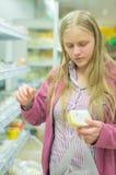 Junge Frau nahe Regalen mit Käse im System Lizenzfreie Stockbilder