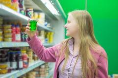 Junge Frau nahe Regalen mit Milch verlässt im System Stockfoto