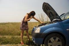 Junge Frau nahe unterbrochenem Auto Stockfotos
