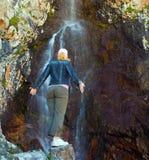 Junge Frau nahe Wasserfall in den Bergen, Ala-Archa, Kyrgyzst Stockfotografie