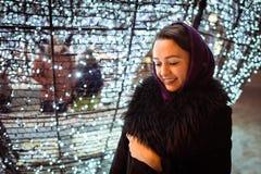 Junge Frau nahe Weihnachtsdekorationen lizenzfreies stockfoto