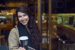 Junge Frau in nippendem Kaffee der braunen Jacke Lizenzfreie Stockfotografie