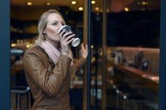 Junge Frau in nippendem Kaffee der braunen Jacke Lizenzfreies Stockbild