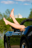 Junge Frau oder ihre Fahrwerkbeine in einem Cabriolet Stockfotos