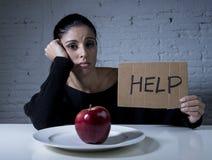 Junge Frau oder jugendlich schauende Apfelfrucht auf Teller als Symbol der verrückten Diät in der unausgewogenen Ernährung Stockfotos