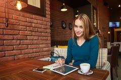 Junge Frau passt Video auf digitaler Tablette während des Restes in der modernen Kaffeestube auf Stockbilder