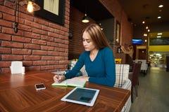 Junge Frau passt Video auf digitaler Tablette während des Restes in der modernen Kaffeestube auf Stockbild