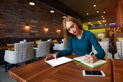Junge Frau passt Video auf digitaler Tablette während des Restes in der modernen Kaffeestube auf stockfotografie