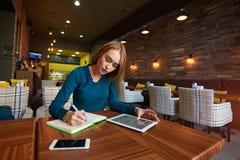 Junge Frau passt Video auf digitaler Tablette während des Restes in der modernen Kaffeestube auf Lizenzfreie Stockfotografie