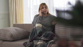 Junge Frau Plys-Größe, die beim Sprechen am intelligenten Telefon zuhause sitzt onder Decke auf dem Sofa lächelt Plusgrößenfrau stock video footage