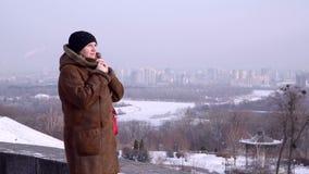 Junge Frau am Rand des Berges, der über der Stadt schaut stock video