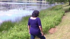 Junge Frau am Rand von einem See stock footage