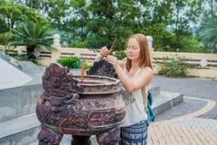 Junge Frau Reisender, der in der höflichen Aktion mit Räucherstäbchen am Buddhismustempel in Vietnam betet stockbilder