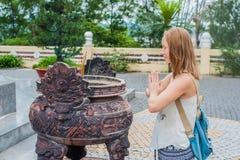 Junge Frau Reisender, der in der höflichen Aktion mit Räucherstäbchen am Buddhismustempel in Vietnam betet lizenzfreies stockfoto