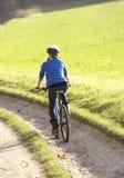 Junge Frau reitet ihr Fahrrad im Park Stockfotografie